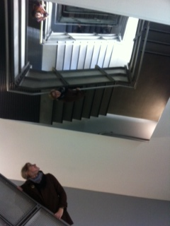 a woman looks up towards a staircase filled with mirrors
